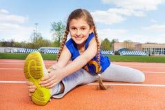 Adolescente feliz que estira las piernas en el estadio Imagen de archivo libre de regalías