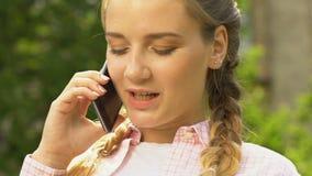 Adolescente feliz que fala no telefone, apontando a data com noivo, fim acima filme