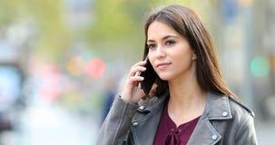 Adolescente feliz que habla en el teléfono en la calle