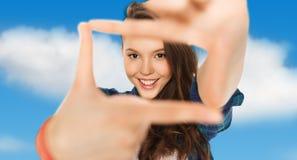 Adolescente feliz que hace el marco de fingeres Fotografía de archivo
