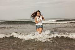Adolescente feliz que juega con el agua en la costa Fotos de archivo libres de regalías