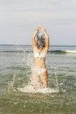 Adolescente feliz que juega con el agua en la costa Fotografía de archivo libre de regalías