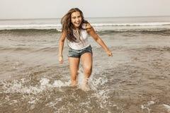 Adolescente feliz que juega con el agua en la costa del bea Foto de archivo