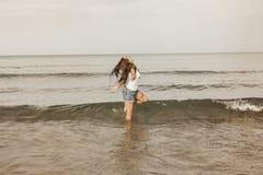 Adolescente feliz que juega con el agua en la costa del bea Imagen de archivo libre de regalías