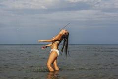 Adolescente feliz que juega con el agua en la costa del bea Fotografía de archivo