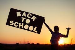 Adolescente feliz que juega en el campo en el tiempo de la puesta del sol Imagenes de archivo