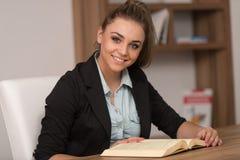 Adolescente feliz que lee un libro en biblioteca Fotos de archivo