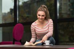 Adolescente feliz que lee un libro en café Foto de archivo libre de regalías