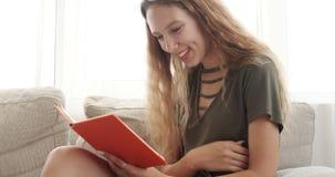 Adolescente feliz que lee un libro en casa almacen de video