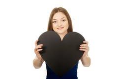 Adolescente feliz que lleva a cabo el corazón de papel Foto de archivo