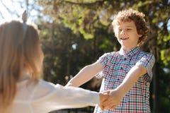Adolescente feliz que lleva a cabo las manos de su hermana Fotografía de archivo