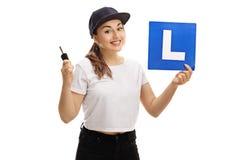 Adolescente feliz que lleva a cabo una llave del coche y una L-muestra Fotografía de archivo