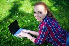 Adolescente feliz que miente con el ordenador portátil en hierba en parque Imágenes de archivo libres de regalías