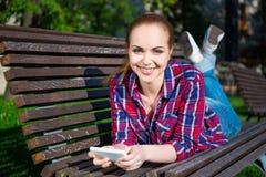 Adolescente feliz que miente con el teléfono elegante en banco en parque Fotografía de archivo