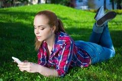 Adolescente feliz que miente con el teléfono elegante en hierba en parque Imagenes de archivo