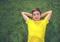 Adolescente feliz que miente en el césped verde tiro del top Imágenes de archivo libres de regalías