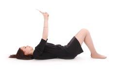 Adolescente feliz que miente en el piso con PC de la tableta Foto de archivo libre de regalías