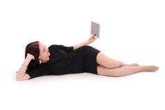 Adolescente feliz que miente en el piso con PC de la tableta Imágenes de archivo libres de regalías