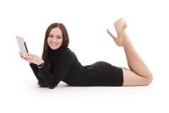 Adolescente feliz que miente en el piso con PC de la tableta Foto de archivo