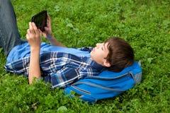 Adolescente feliz que miente en hierba en parque Imagen de archivo