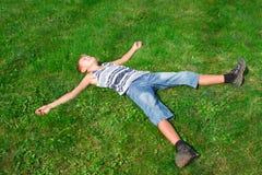 Adolescente feliz que miente en la hierba Fotos de archivo