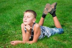 Adolescente feliz que miente en la hierba Fotos de archivo libres de regalías