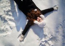 Adolescente feliz que miente en la nieve profunda Imagenes de archivo