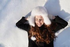 Adolescente feliz que miente en la nieve profunda Foto de archivo libre de regalías