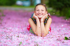 Adolescente feliz que miente en pétalos rosados, jardín de la primavera Foto de archivo