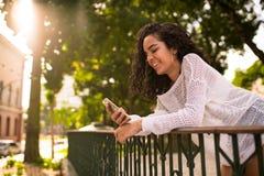 Adolescente feliz que mira el teléfono móvil Foto de archivo