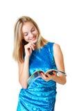 Adolescente feliz que mira en el diario Fotos de archivo