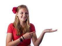 Adolescente feliz que muestra algo en la palma de su mano Imagen de archivo