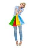 Adolescente feliz que muestra bolsos de compras Foto de archivo libre de regalías