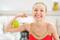 Adolescente feliz que muestra el bíceps y la manzana Imagenes de archivo