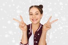Adolescente feliz que muestra el signo de la paz sobre nieve Foto de archivo