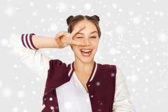 Adolescente feliz que muestra el signo de la paz sobre nieve Imágenes de archivo libres de regalías