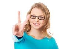 Adolescente feliz que muestra la muestra de la victoria Fotografía de archivo libre de regalías