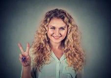 Adolescente feliz que muestra la victoria o el signo de la paz Imágenes de archivo libres de regalías