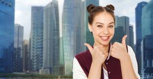 Adolescente feliz que muestra los pulgares para arriba sobre ciudad Imagenes de archivo