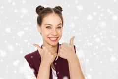 Adolescente feliz que muestra los pulgares para arriba sobre nieve Fotografía de archivo libre de regalías