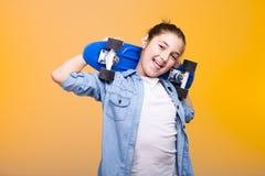 Adolescente feliz que muestra su lengua con un monopatín en hombros Foto de archivo libre de regalías