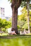 Adolescente feliz que oculta en el árbol Fotos de archivo