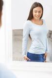Adolescente feliz que olha a reflexão no espelho fotografia de stock royalty free