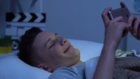 Adolescente feliz que olha vídeos engraçados no smartphone e no riso, encontrando-se na cama vídeos de arquivo