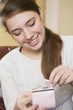 Adolescente feliz que pone el dinero en el monedero Imagenes de archivo