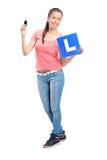Adolescente feliz que prende uma chave do carro e um L placa fotografia de stock royalty free