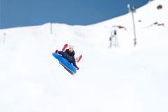Adolescente feliz que resbala abajo en el tubo de la nieve Fotos de archivo