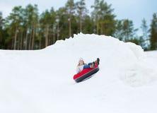 Adolescente feliz que resbala abajo en el tubo de la nieve Foto de archivo libre de regalías