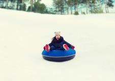 Adolescente feliz que resbala abajo en el tubo de la nieve Imagenes de archivo