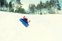 Adolescente feliz que resbala abajo en el tubo de la nieve Foto de archivo